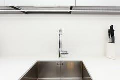 在不锈钢厨房水槽的现代设计师镀铬物水龙头 明亮的白色厨房内部  免版税图库摄影
