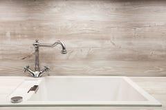 在不锈钢厨房水槽的现代设计师镀铬物水龙头 图库摄影