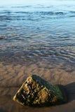 在与一个唯一岩石的海滩附近浇灌 免版税库存照片