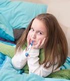 在与一个温度计的床上的一个病的婴孩在他的嘴 库存照片