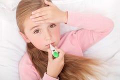 在与一个温度计的床上的病的女孩在嘴 库存照片