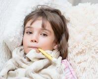 在与一个温度计的床上的病的女孩在嘴 免版税库存图片