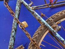 在与一个老金属链子的蓝色绘的一辆老金属自行车的片段在黄色锁,在深蓝背景 免版税库存图片