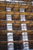 在与专栏的一个历史建筑附近有木装饰的金属脚手架被修造的恢复工作和整修门面的 图库摄影