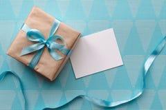 在与丝带的包装纸包裹的礼物盒在与贺卡的蓝色背景 o 免版税库存图片