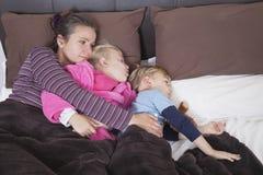 在与两个孩子的床上的母亲 库存图片