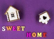 在与两个玩具木房子的桃红色背景计划的词组`甜家庭` 免版税库存图片