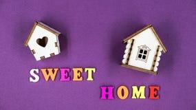 在与两个玩具木房子的桃红色背景计划的词组`甜家庭` 库存图片