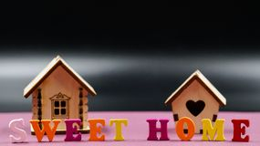 在与两个玩具木房子的桃红色背景计划的词组`甜家庭` 库存照片