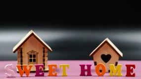 在与两个玩具木房子的桃红色背景计划的词组`甜家庭` 免版税图库摄影