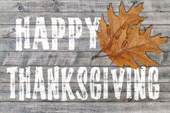 在与两叶子的木板背景写的白色愉快的感恩 免版税库存照片