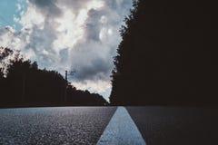 在与云彩柏油路的雨天空以后 库存图片