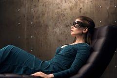 在与他的一把椅子的美丽的少妇注视闭合 黑鞋带面具 免版税库存图片
