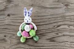 在与兔宝宝的篮子收集的复活节彩蛋 库存图片