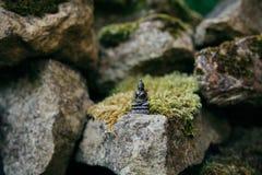 在与其他岩石的一个大岩石安置的微小的菩萨雕象 图库摄影