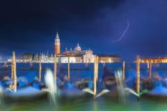 在与剧烈的天空和照明设备的蓝色小时圣乔治Maggiore教会和长平底船在威尼斯,意大利 在教会的焦点 图库摄影