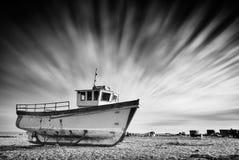 在与剧烈长的一个pebbled海滩搁浅的老渔船 免版税图库摄影