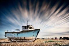 在与剧烈长的一个pebbled海滩搁浅的老渔船 图库摄影