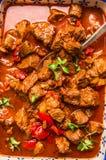在与匙子,顶视图的红色蕃茄辣椒粉调味汁炖的牛肉 库存图片