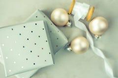 在与圆点样式的灰色锡箔包裹的被堆积的礼物盒 有白色丝绸丝带的,圣诞节球木短管轴 免版税库存图片