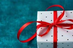 在与圆点红色丝带的灰色锡箔包裹的典雅的礼物盒在蓝色背景 圣诞节新年华伦泰 免版税库存图片