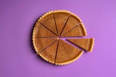 在与在紫色背景分离的,一件的切片切的南瓜饼的看法上 最低纲领派食物图象 感恩 图库摄影