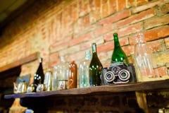 在与垂悬在砖的五颜六色的玻璃瓶的黑暗的木架子安置的古色古香的照相机的旁边照片 免版税库存照片