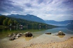 在与多云天空, Bohijn湖,斯洛文尼亚期间,有的冷的山湖在上面前面和雾的石头 库存图片