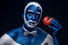 在与多雪的拿着蕃茄的头发和胡子的蓝色颜色绘的人 库存照片