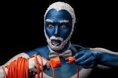 在与多雪的头发和胡子的蓝色颜色绘的人拿着与插座的电源线 免版税图库摄影