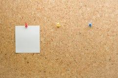 在与大头钉别针和等待的pape的黄柏板张贴的纸牌 免版税库存照片