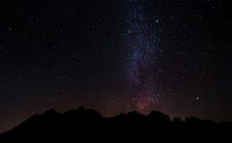 在与天空的晚上现出轮廓山峰有很多星和银河 库存图片