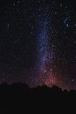 在与天空的晚上现出轮廓山峰有很多星和银河 库存照片