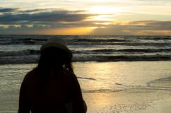 在与太阳上升和反射在海水的阳光的一个海滩现出轮廓的前景的一名妇女 免版税库存图片