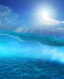 在与太阳光亮的天空和沙丘地面的清楚的海水下 图库摄影