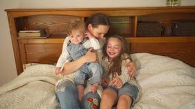在与她俏丽的女儿和儿子的床上的可爱的母亲 手扶的射击 股票录像