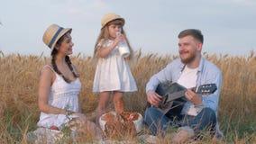 在与她的年轻母亲和愉快的爸爸的远足期间在乡下野餐的家庭,女孩喝从瓶的牛奶 影视素材
