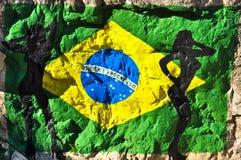 在与妇女剪影的岩石绘的巴西旗子  免版税图库摄影