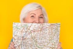 在与嬉戏的地图的黄色墙壁覆盖面孔隔绝的资深妇女旅客演播室 库存照片