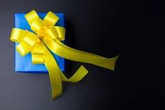 在与弓的颜色纸包裹的当前礼物盒设计在bl 免版税库存照片