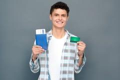 在与快乐的票和信用卡微笑的灰色墙壁旅游业概念身分藏品护照隔绝的人 库存图片