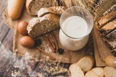 在与成份的一张木桌安置的一个玻璃瓶的顶视图牛奶 免版税库存图片