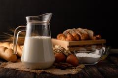 在与成份的一张木桌安置的水罐的牛奶 图库摄影