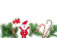 在与拷贝空间的白色背景隔绝的与棒棒糖的杉树分支和圣诞老人圣诞节框架您的文本的 库存照片