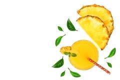 在与拷贝空间的白色背景隔绝的玻璃和菠萝切片的菠萝汁您的文本的 顶视图 免版税图库摄影