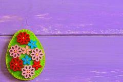 在与拷贝空间的紫色木背景隔绝的美丽的花卉复活节彩蛋文本的 毛毡蛋工艺 库存图片