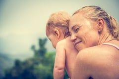 在与拷贝空间的假期时照顾恳切拥抱她的婴孩 象征婴孩关心和爱的概念性图片 免版税图库摄影