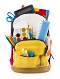 在与推出的学校用品的白色backgorund隔绝的背包 库存照片