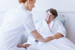 在与握她的手的年轻有用的护士的白色医院病床上的资深灰色妇女 免版税图库摄影