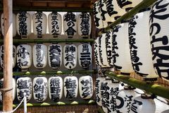 在与日本文字的竹木筏排队的日文报纸灯笼和在一个寺庙旁边垂悬在东京,日本 免版税库存图片
